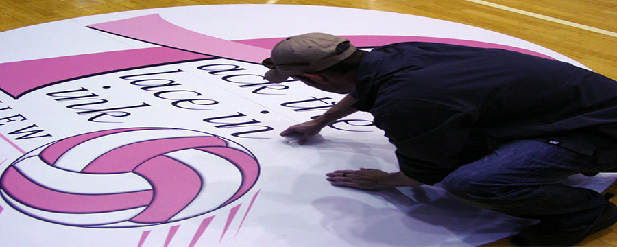 Custom printed floor graphics being installed on gym floor.